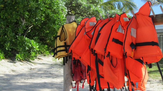 Orange life jackets in a row.. wit a few yellow ones on the end
